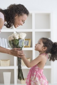 Girl Giving Her Mother Bouquet of Roses --- Image by © Royalty-Free/Corbis